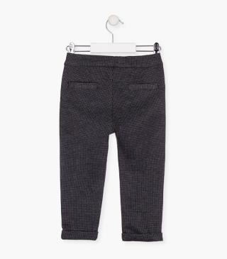 Houndstooth trousers with roll-up cuff.