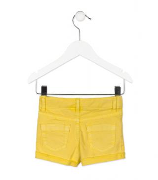 Short en sarga de color amarillo con rotos y parches.