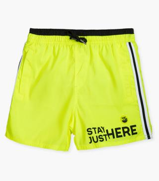 Neon yellow swim trunks with silicone tag.
