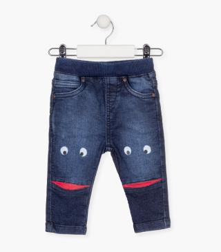 Trousers with printed faces on the legs.