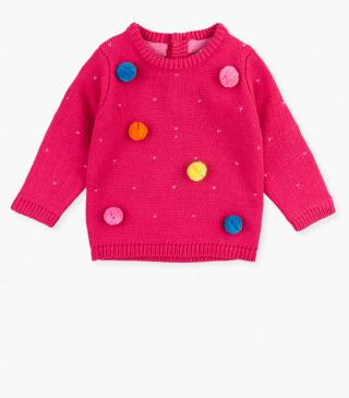 Knit jumper with coloured pompoms.