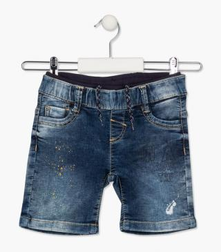 Denim shorts with paint splatter.