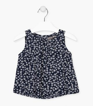 Blue sleeveless blouse with flowers.